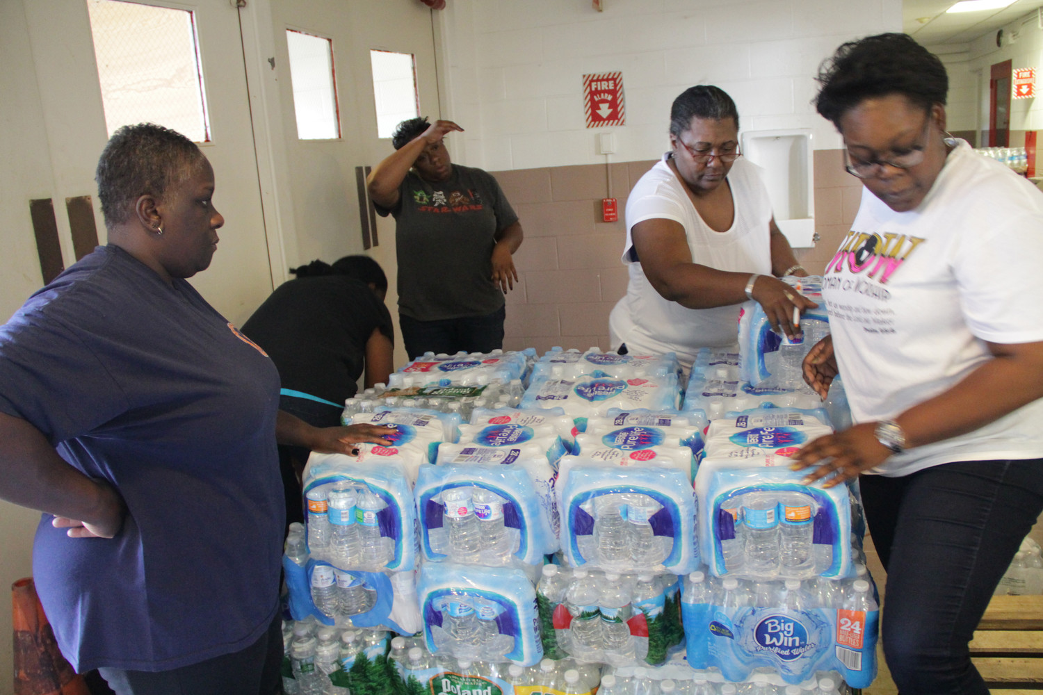 Zion Cathedral volunteers, from left Melissa R. Harris, Rogina Garcia, Tracey Matthews and Regina Roundtree stacked pallets of donated water to be shipped to hurricane victims.