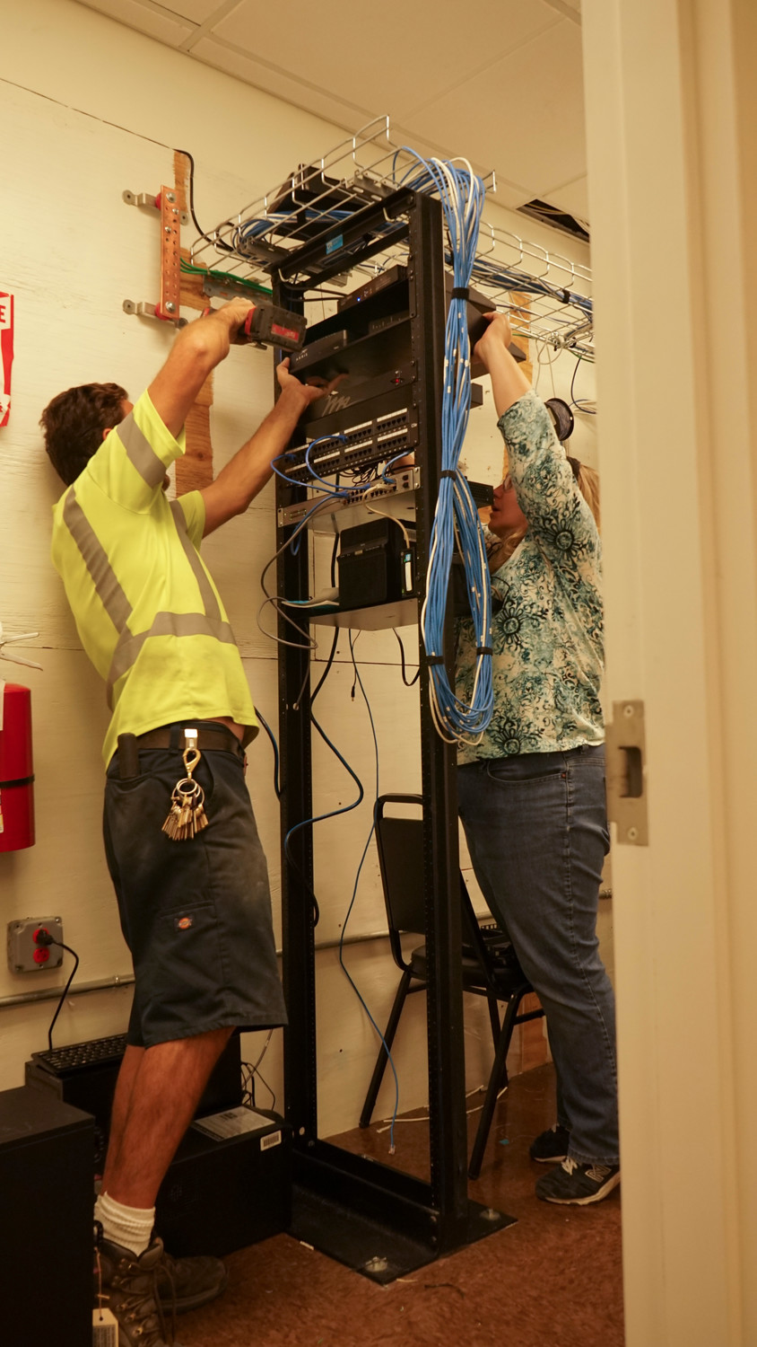 Village DPW worker Bill Boyce, left, helped Susan Hebel as they installed IT equipment on the village's server racks.