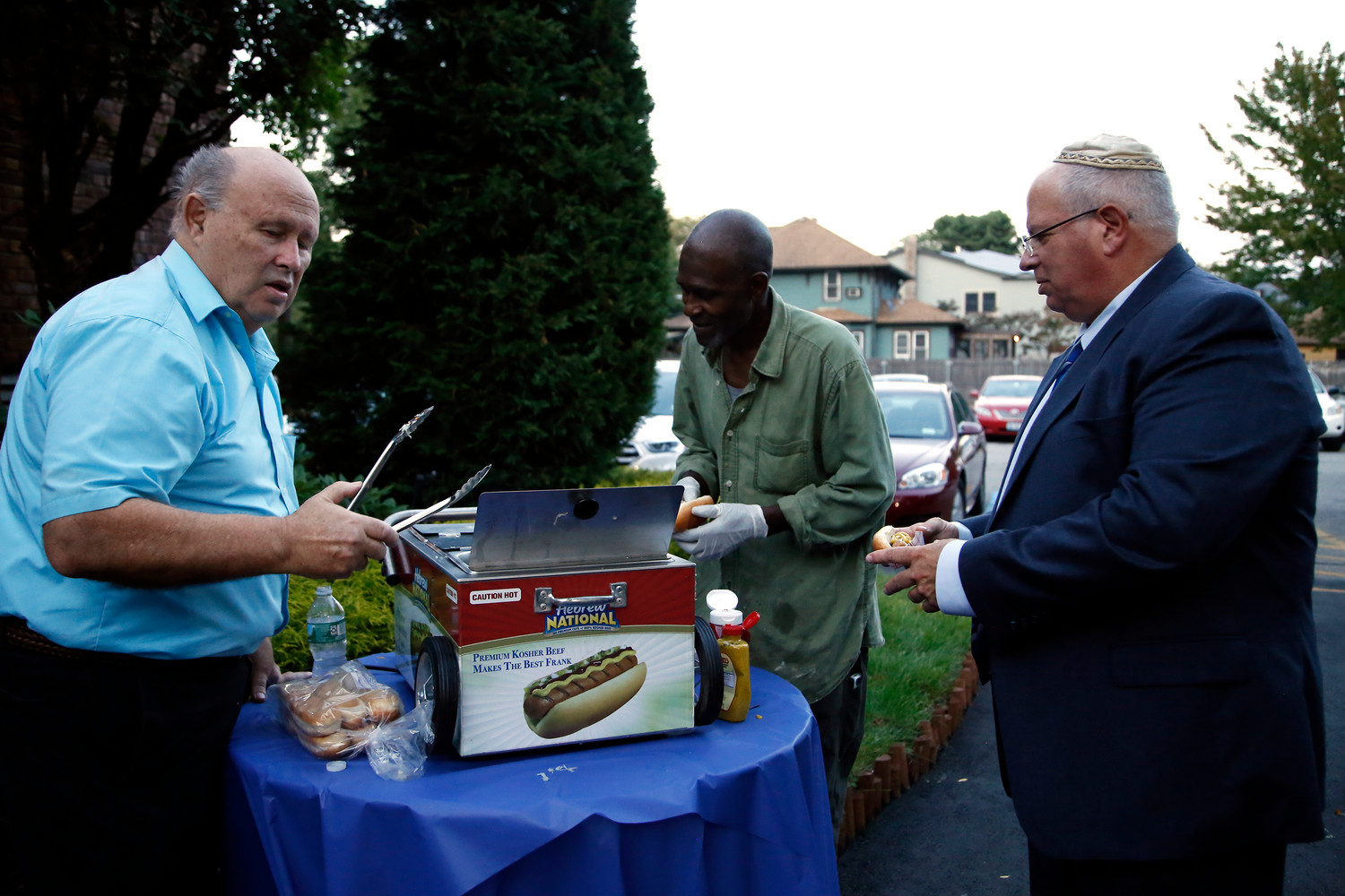 Peter Brandenberger served Hebrew National hotdogs to Cosmo Holmes and Cantor Dan Rosenfeld.