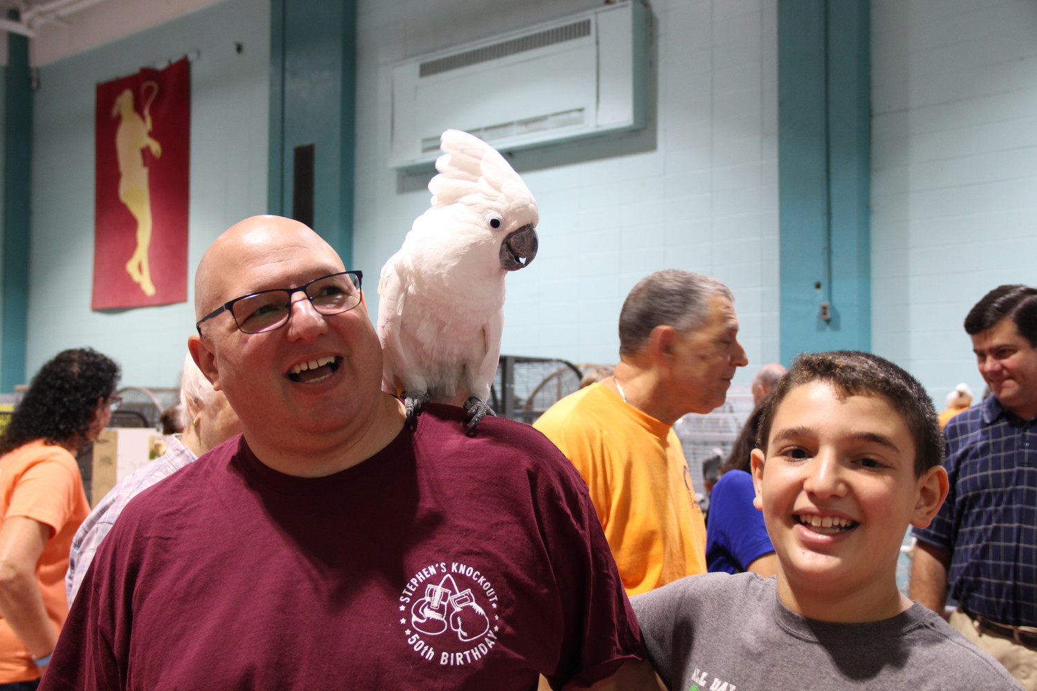 Steven Seligson and his son Ethan had fun with Zachary the cockatoo during the Parrot Expo on Saturday at the Freeport Recreation Center.