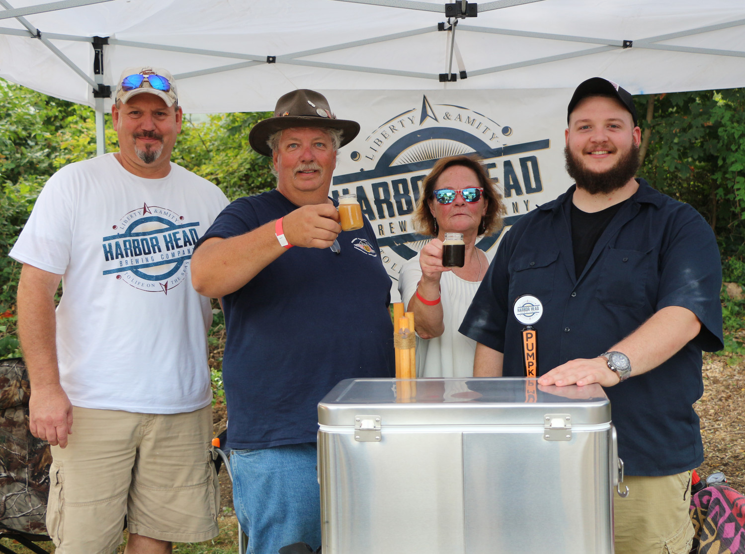 Joining in the festivities were, from left, Glenn Schug, John Cools, Kathy Schatz and Kyle Schug enjoy a sample of beer from the Harbor Head Brewery.  Harbor Head makes a variety of different flavored brews, including mango alopeno and pumpkin.