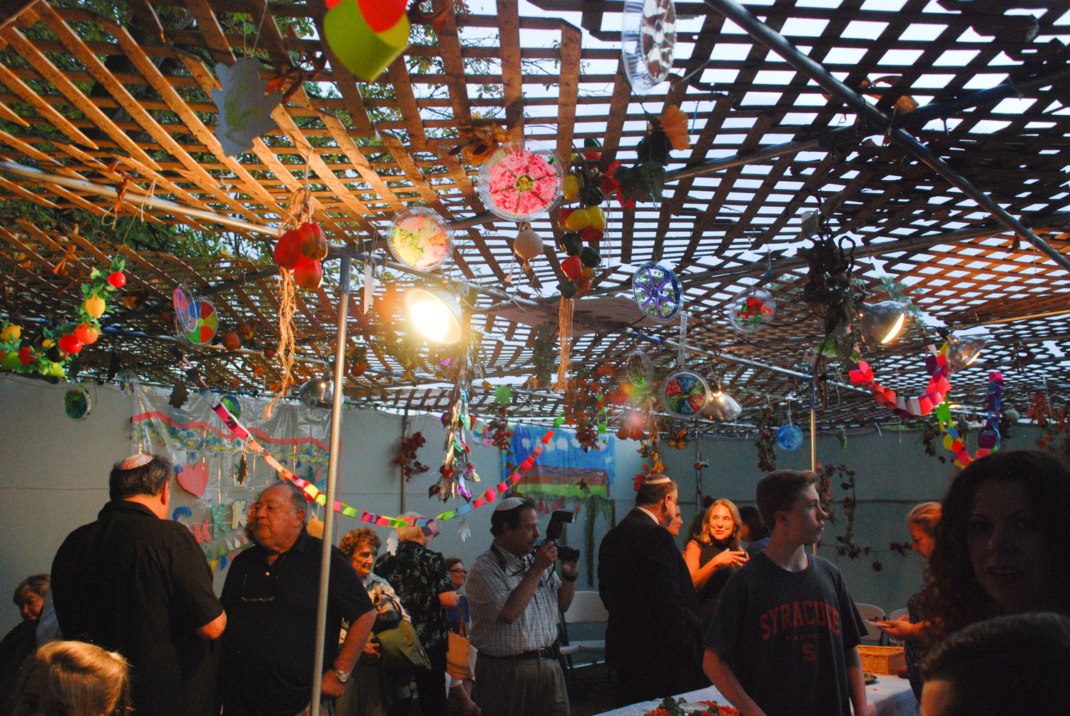 The Sukkah's ceiling was decorated with colorful art projects from the Temple's Hebrew school students.