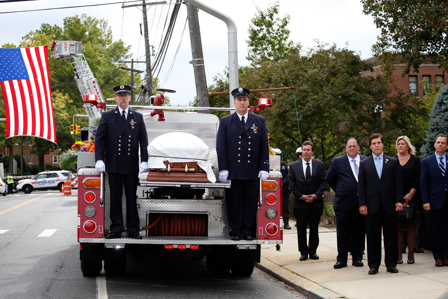 Former Lynbrook Fire Department Captain Joe Rice, left, and firefighter Mike Kenny stood on a fire truck that transported the body of Mayor William Hendrick from Perry Funeral Home in Lynbrook to St. Raymond's Roman Catholic Church in East Rockaway for his funeral Mass on Monday. Village Clerk John Giordano, third from left, Trustee Mike Hawxhurst, acting Mayor and former Deputy Mayor Alan Beach, Trustee Ann Marie Reardon and Trustee Hilary Becker also paid their respects.