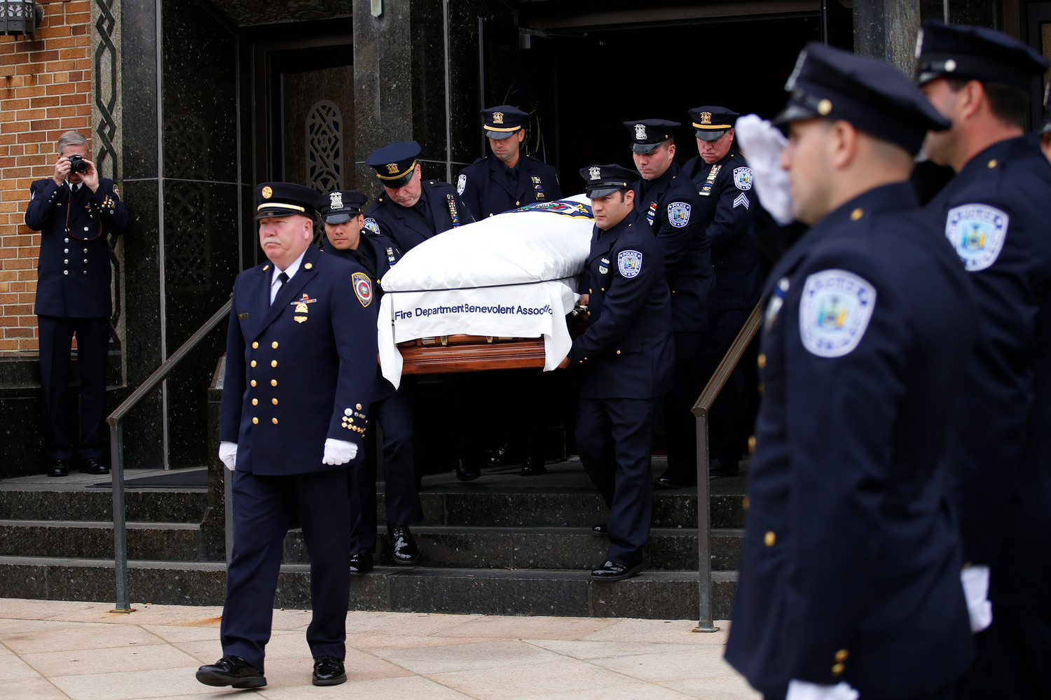 Lynbrook Fire Chief Carl Lengel led police officers as they carried Hendrick's casket out of St. Raymond's.