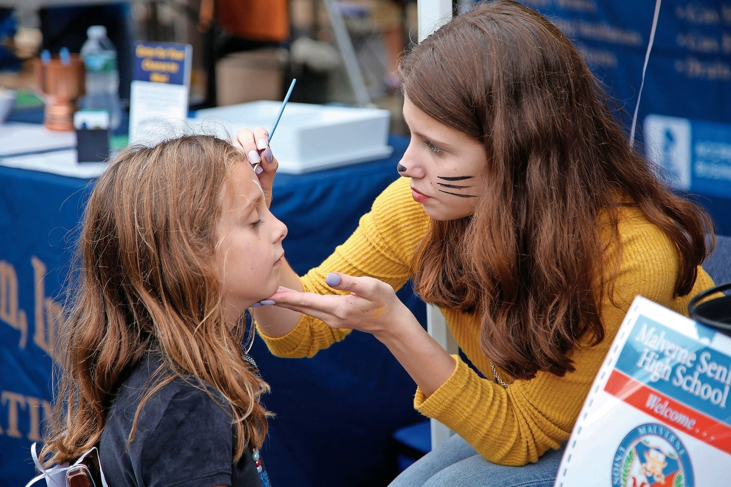 Liz Ray painted 6-year-old Caroline Lampiasi's face at Malverne High School's table.
