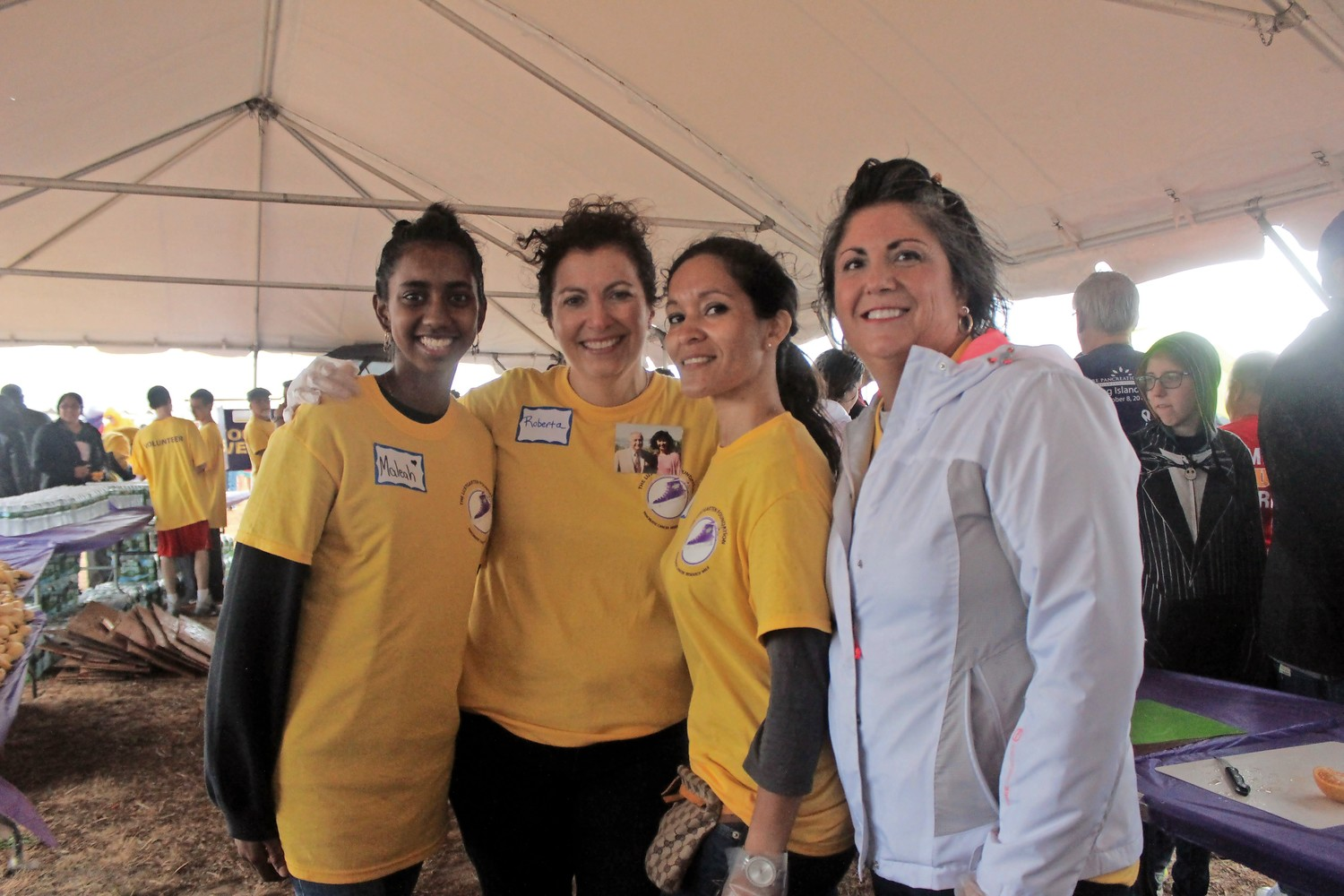 Volunteers from the Lustgarten Foundation were set up under large tents providing fresh fruit, water and shelter from the downpour. From left, Maleah Ishmael, Roberta Perrone, Eva Rodriquez and Rita Leo.