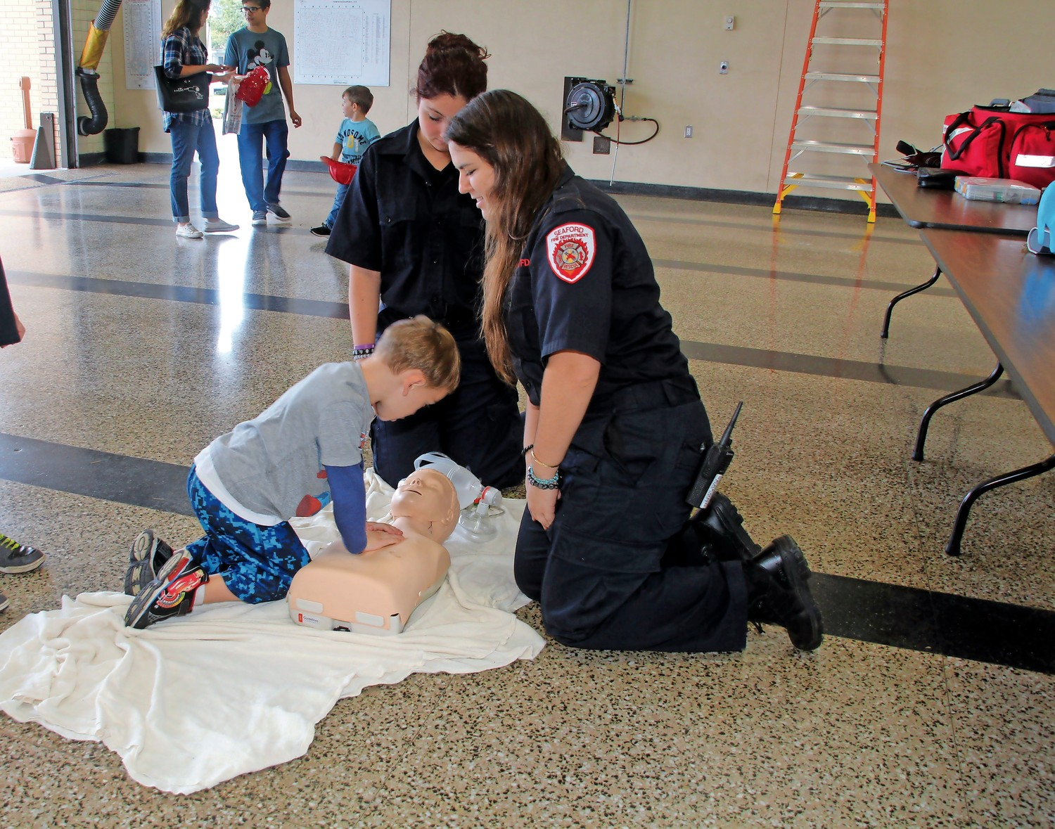 Conor Valentine, 5, gets instructions from Fire Medic Morgan Chipurnoi and Nicole Esposito, a fire medic in training.
