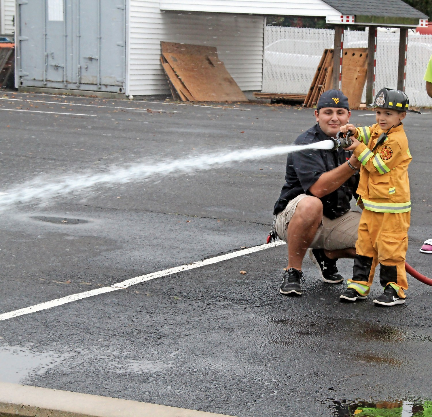 Ryan Kind, 5, gets instructions from Seaford Firefighter Joe Bongiovi on how to direct a hose line.
