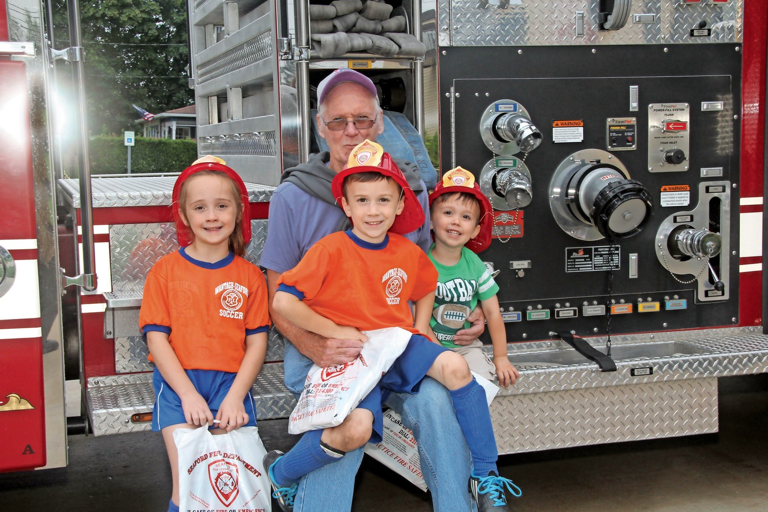 Matt Strong and his grandchildren Katie, 7, Will, 5, and Mikey, 2, had fun at the open house after they got a tour of the fire truck.