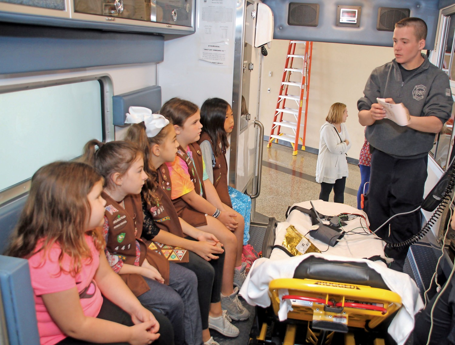 Seaford Fire Medic Tommy Reid explained some of the medical tools that are used in an emergency to Girl Scout Troops 3441 and 3060 at the department's open house. From left, Erin Comiskey, Hannah Curry, Amelia Curry, Emily Comiskey and Abigail Wind.