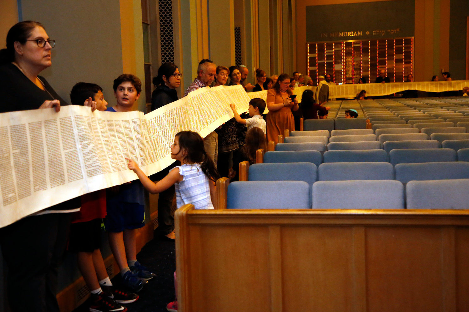 Children got a close-up look at the Torah as it was rolled out during a service at Central Synagogue–Beth Emeth on Oct. 11. The unrolling was in preparation for the celebration of Simchat Torah on Oct. 12, a Jewish holiday where the year-long Torah-reading cycle is completed and then immediately begun anew.