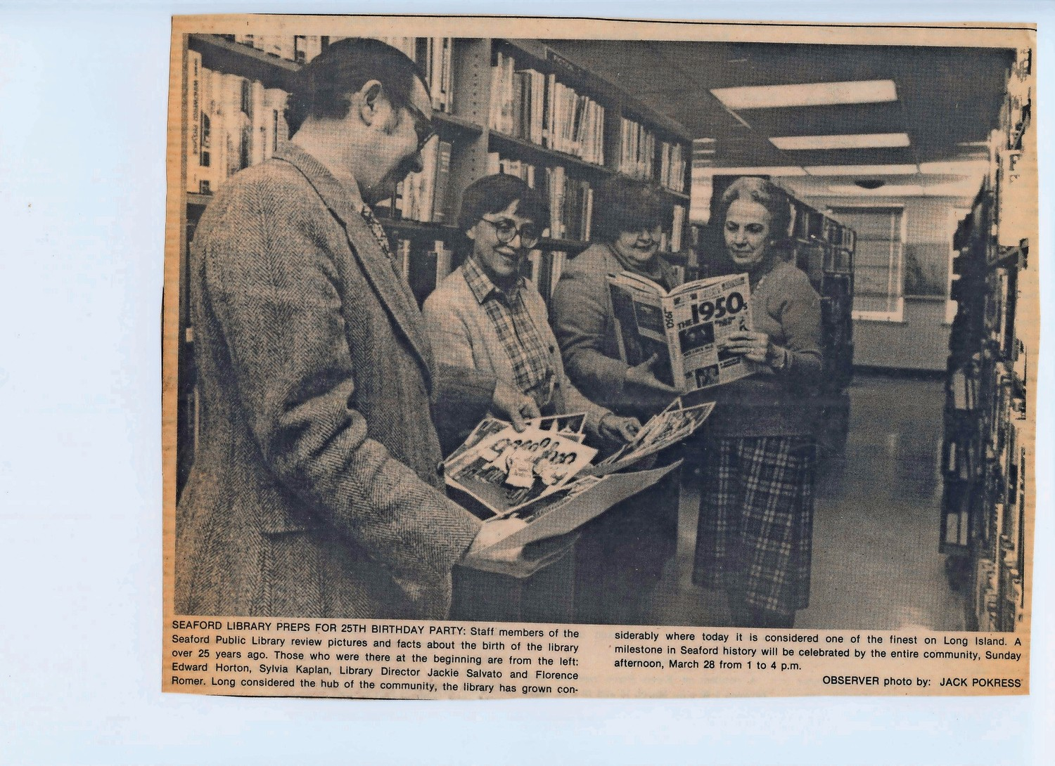 Edward Horton, Sylvia Kaplan, former Library Director Jacqueline Salvato and Florence Romer reviewed photos and facts about the library before its 25th birthday party.