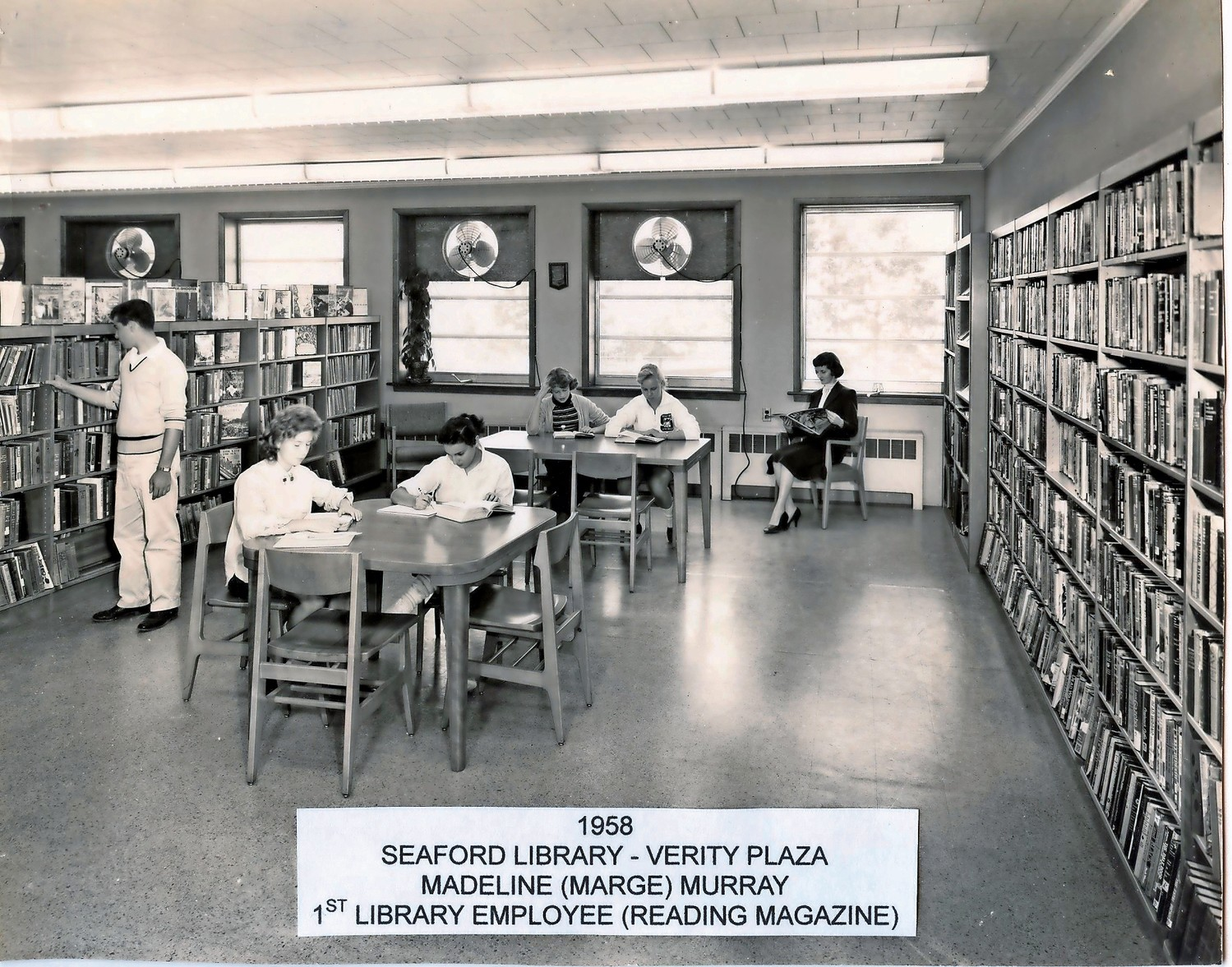 Madeline Murray, far right, the first Seaford Library clerk, read a magazine in the original building, at Verity Plaza, in 1958.