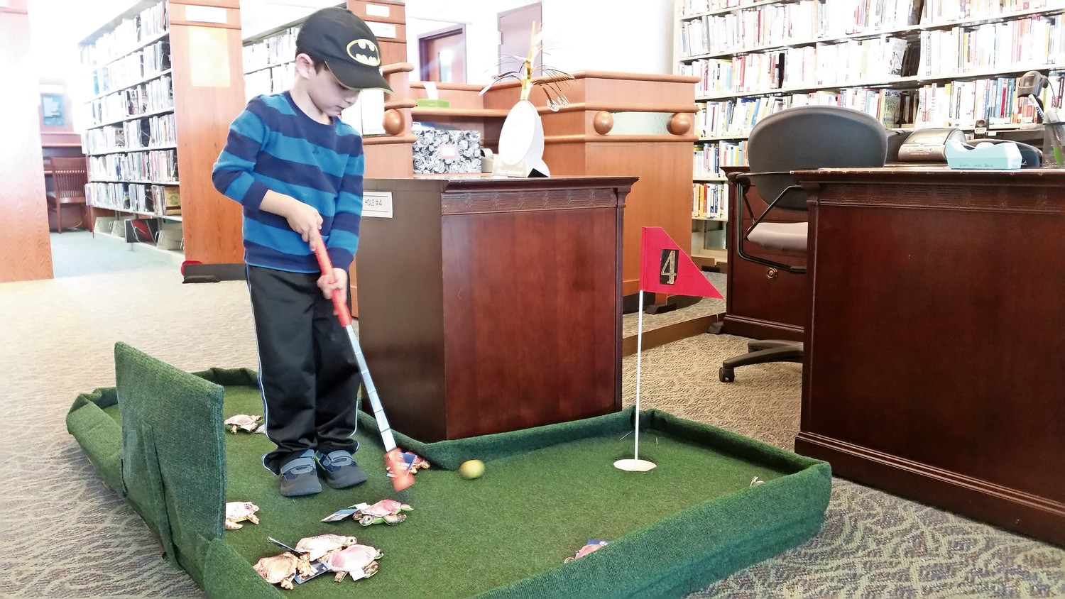 Eli Lax, 4, showed off his putting skills at the library's mini-golf course.