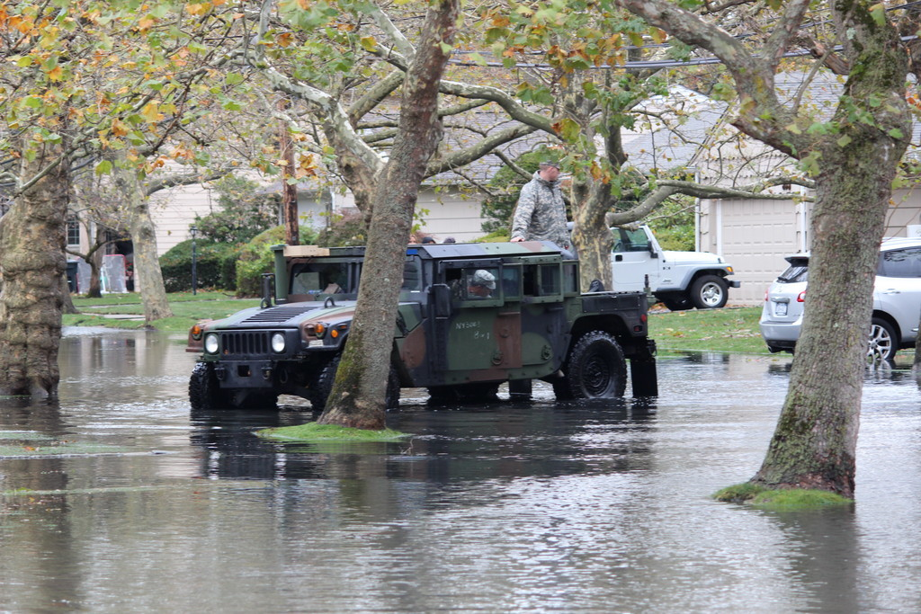 Two National Guardsmen maneuvered their jeep through floodwater on Green Place in Woodmere, two days after Hurricane Sandy.