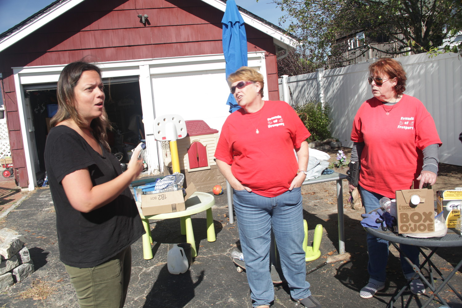 Tess Brunetti, left, Linda Combs Stuerzel, first vice president of Friends of Freeport, and Lois Howes, president of Friends of Freeport, right, chatted after a morning cleanup of Brunetti's yard in Baldwin last Saturday.