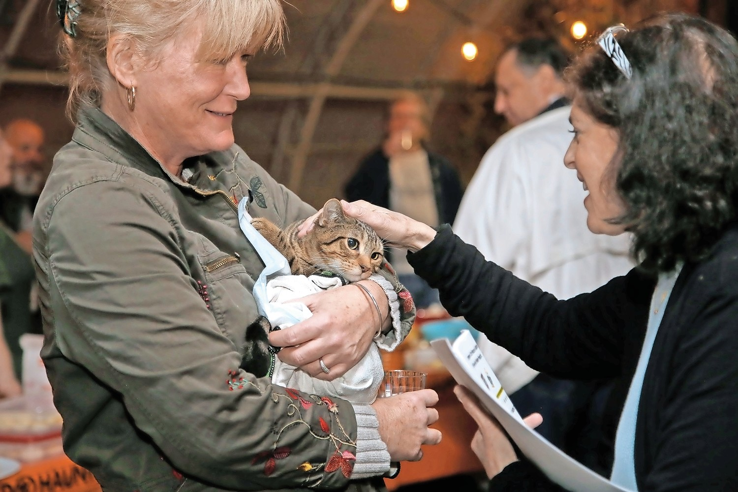 Courageous Cats board member Pat Irizarry, left, and volunteer Deb Wantuch comforted many cats, including Otto, at the Sip and See Fundraiser at Crossroads Farm on Oct. 27.