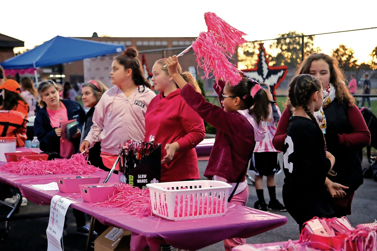 Fifth-grader Emmy Zueto uses pink cheerleading props to attract attention to their booth.
