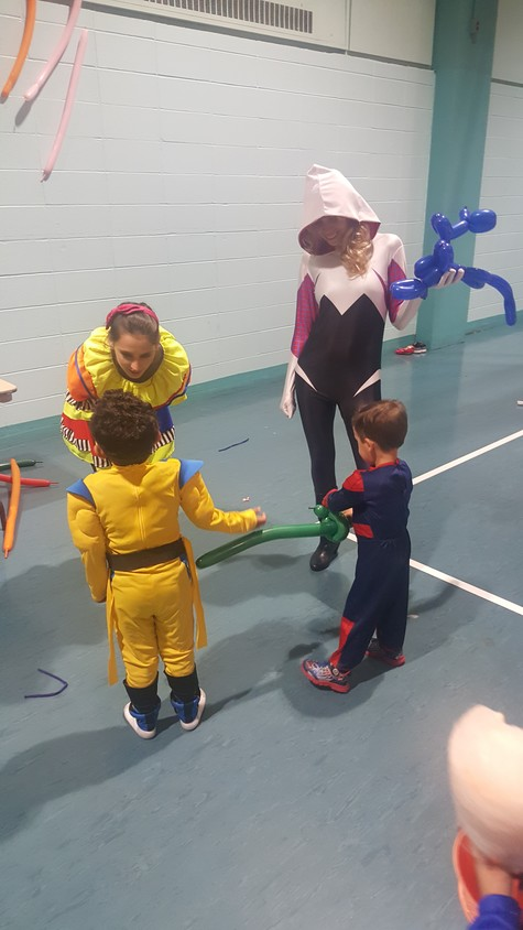 Freeport mom, Lisa Csenscits, right, watches as her two boys, Luis and Edward, ask Bubbles the clown for a balloon sword.