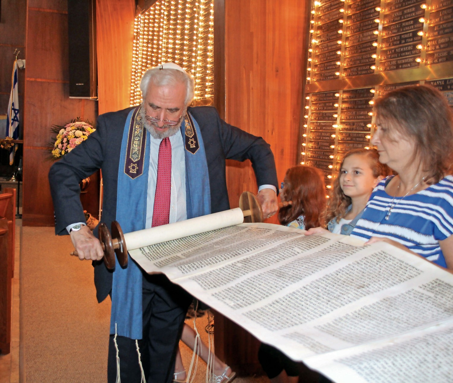 Rabbi Howard Nacht, of Temple B'Nai Torah, looked over a scroll at the temple's Simchat Torah service on Oct. 11. Temple Emanu-El, of East Meadow, will merge with the congregation next July.