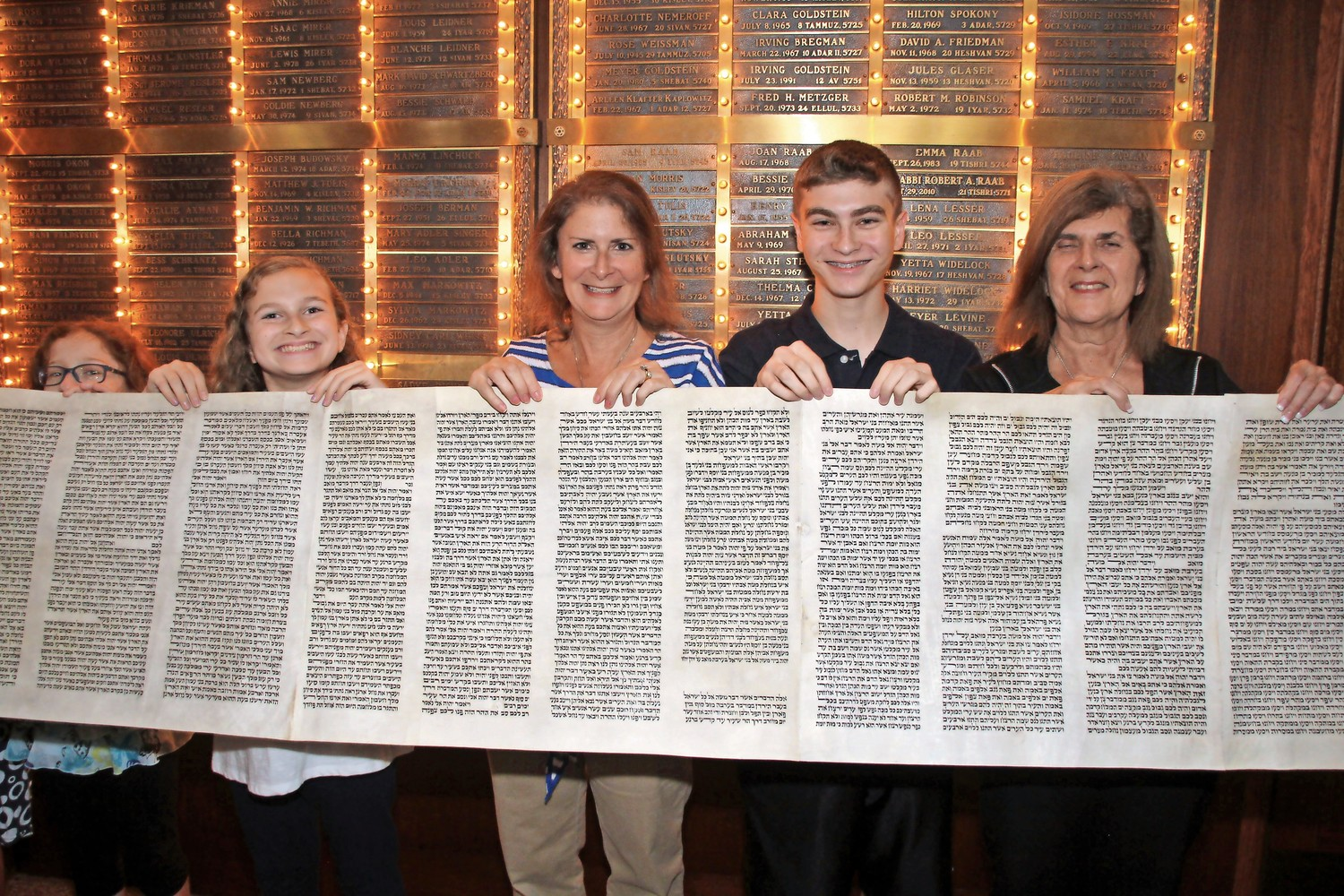 Mandy, left, Amy and Ryan Krauss held the Torah scroll, along with Libby Bienenfeld, far right, at the Simchat Torah services in one of the synagogues' first joint services on Oct. 11.