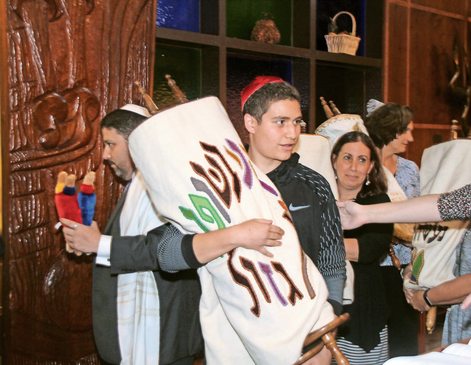 Carrying a Torah scroll, Jacob Scutch carefully held onto it at Simchat service.