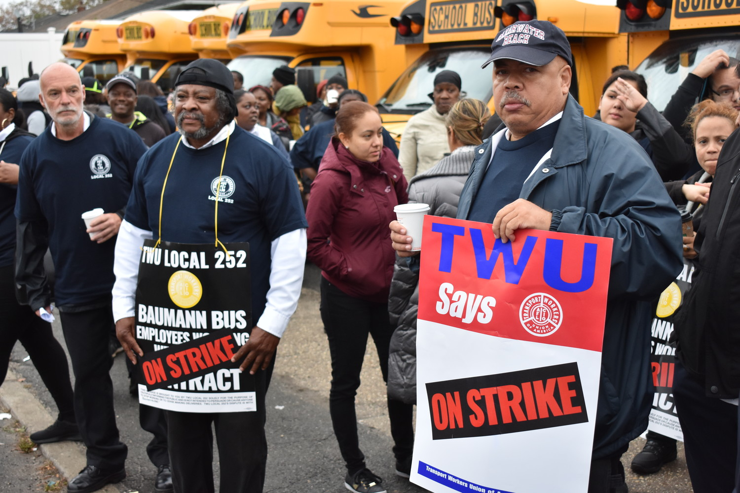 Walter Richardson, with sign on left, and Leonardo Bautista were among the members of Transportation Workers Union Local 252 who went on strike against the Oceanside-based Baumann Bus Company on Monday.
