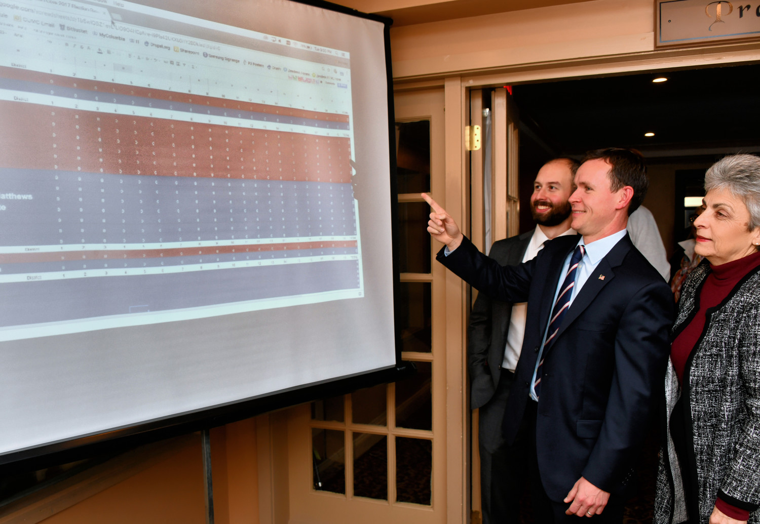 Councilman Nick DiLeo, Candidates Matt Connolly and Zefy Christopoulos look on as results are posted.