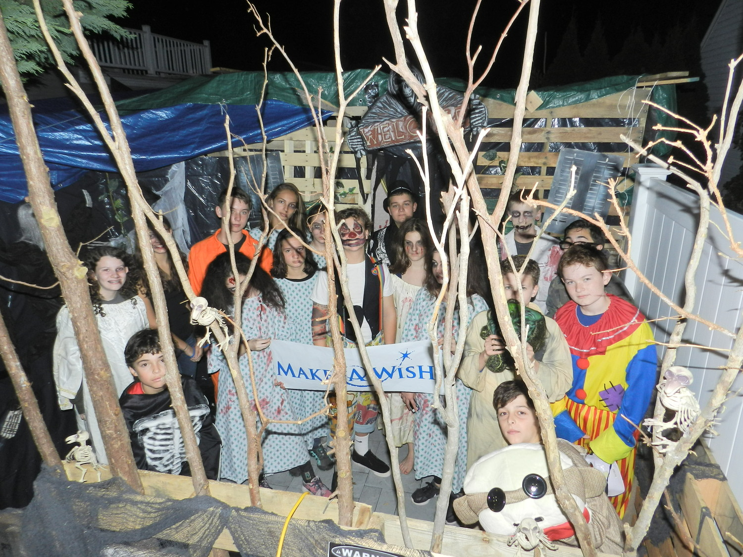 Gavin Lacy, center, dressed as a killer clown, gets a little help from his friends to put up his homemade haunted house.