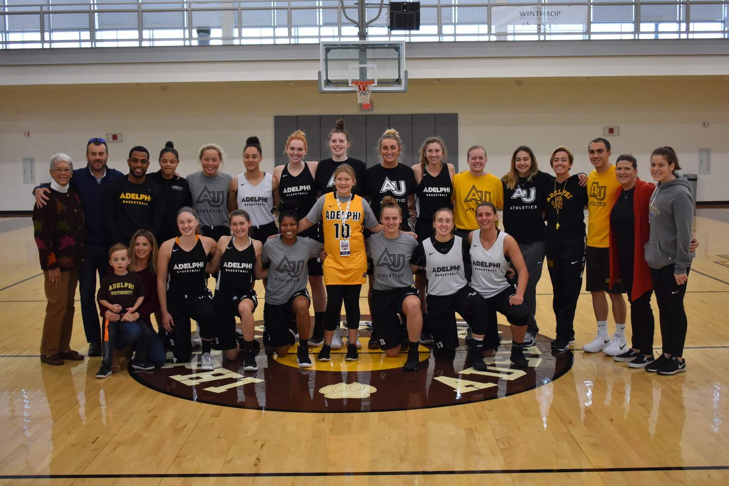 Bianca Onorato, center, was joined by her family and Adelphi student-athletes on the court of the university's recreation center after the ceremonial signing.
