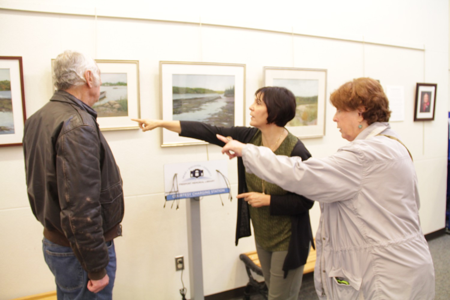 Bill Marinaccio, left talked about his wife's artwork with Freeporters, Laura Schoffer and Lois Howes, right.