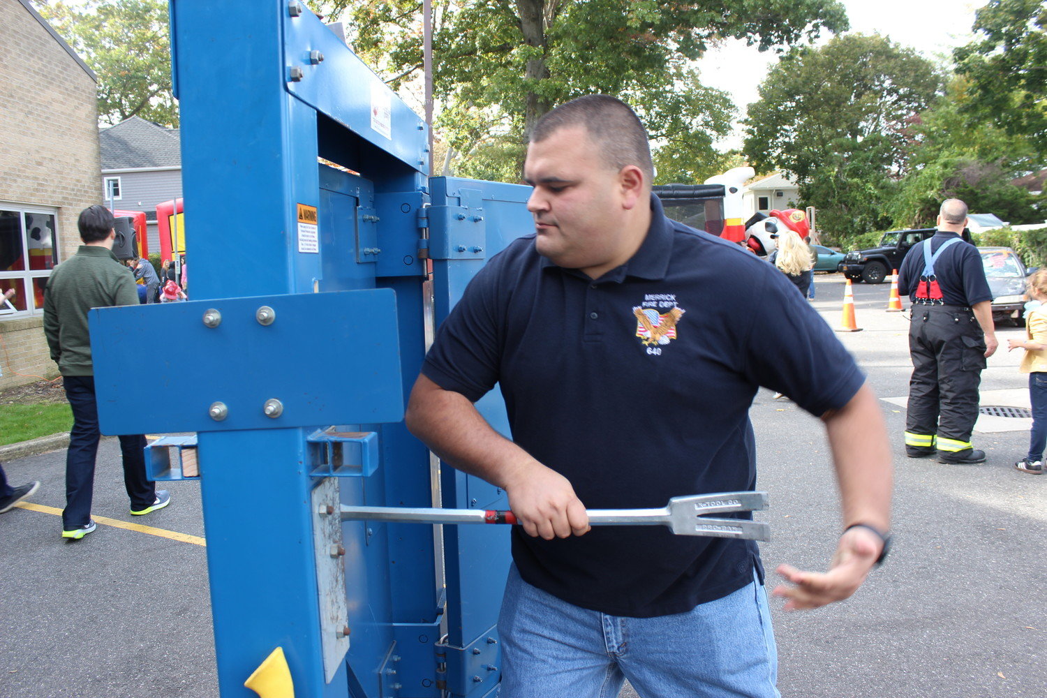 Captain Jeffrey Monsen, of the Merrick Fire Department, simulated the process of breaking into a locked door using a Halligan bar.