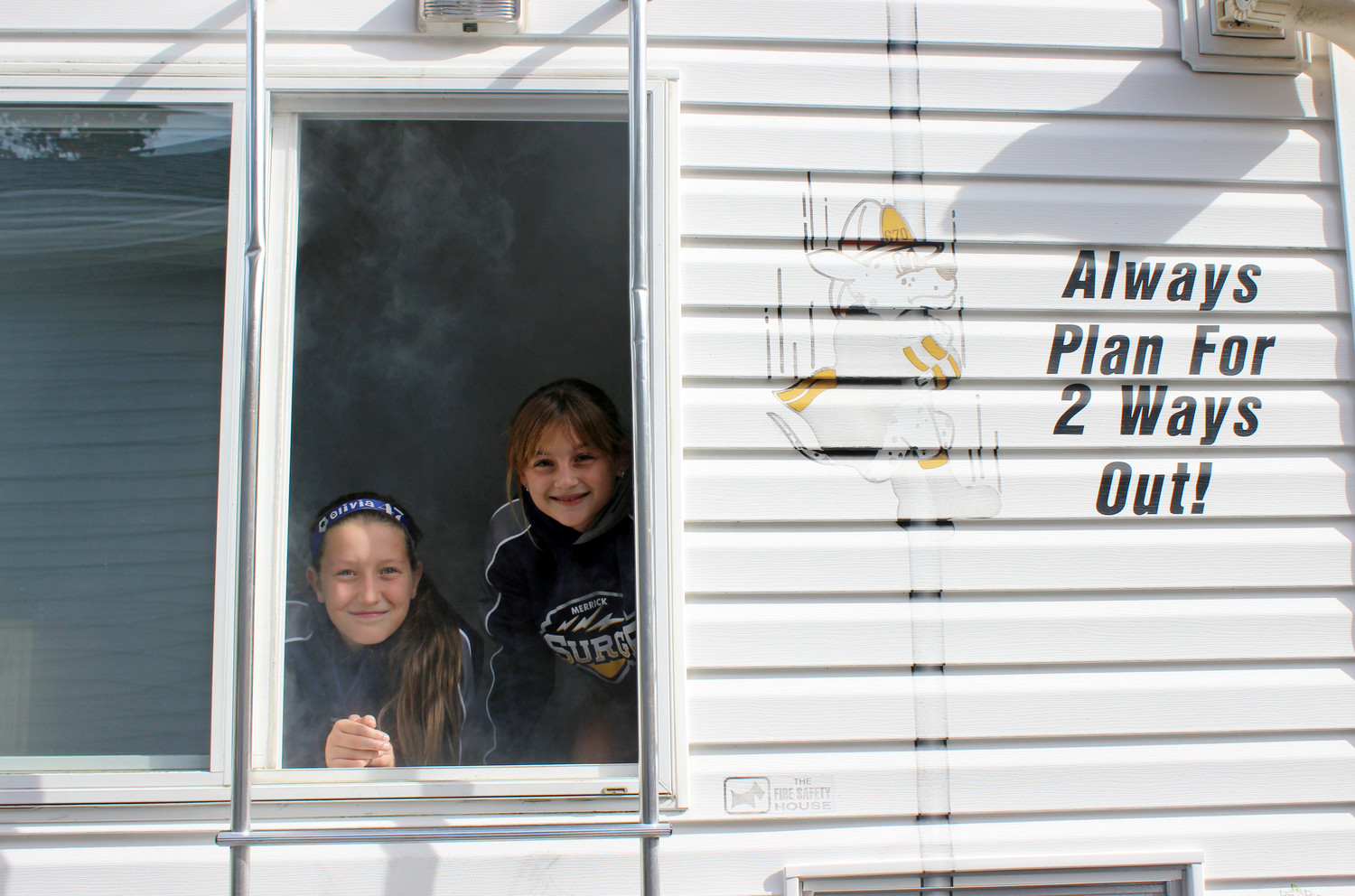 "Olivia Schwartz, 11, left, and Leah Seip, 10, both of Merrick, crawled through a ""safety house,"" which simulates a smoke-filled room during a fire."