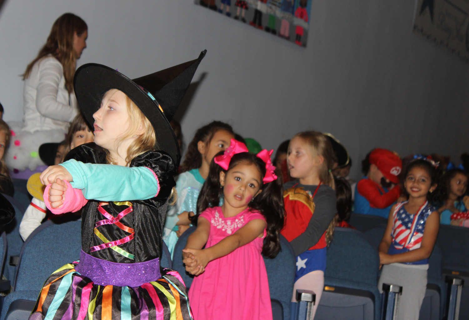 "Reinhard kindergarten students pantomimed stirring a cauldron as they sung the Halloween sung ""Old Mrs. Witch"" for an auditorium full of parents and siblings."