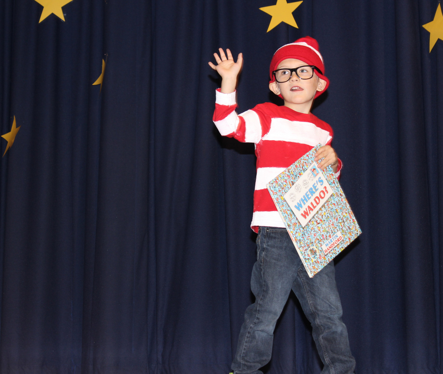 "One kindergartener dressed as Waldo from the classic search-and-find book ""Where's Waldo?"" holding a copy of the book as he marched with his fellow classmates."