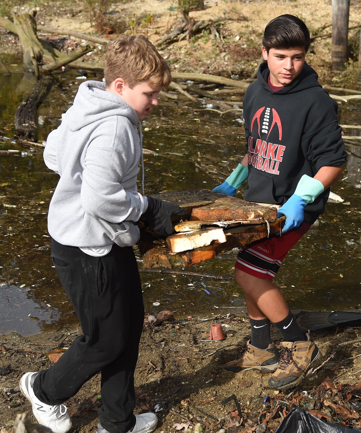 Robert Richard, 13, above, and Matt Anest, 14, carried large plastic disks that were decaying into the soil.