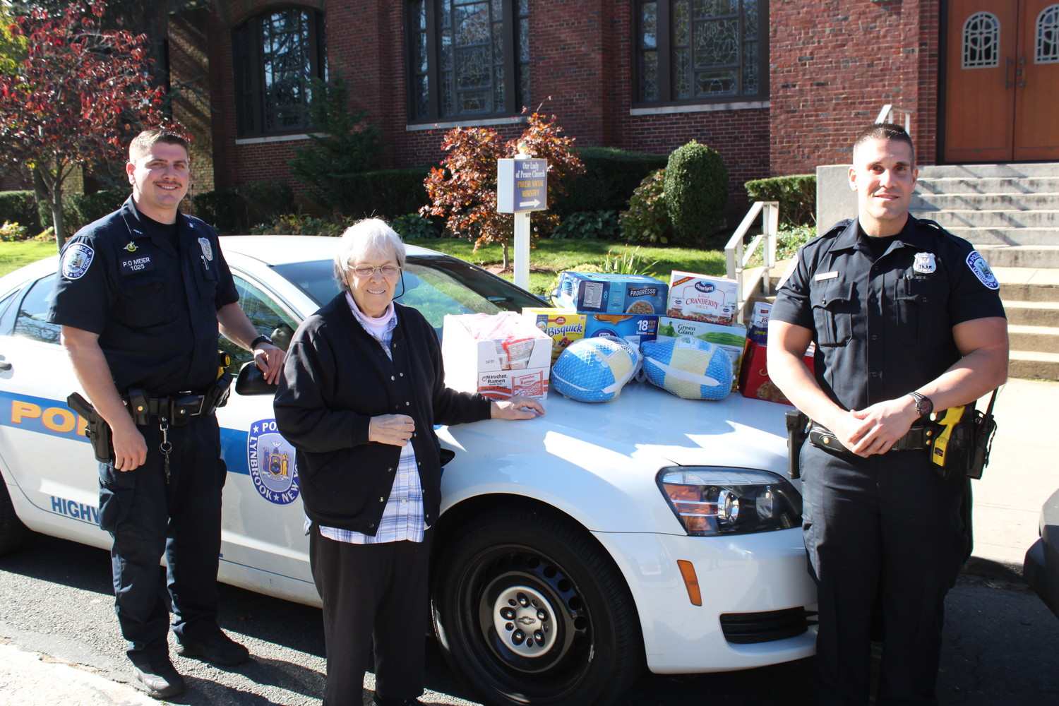 Sister Barbara Faber, center, accepted food pantry donations from Lynbrook Police Officers Robert Meier and Derek Buonora.