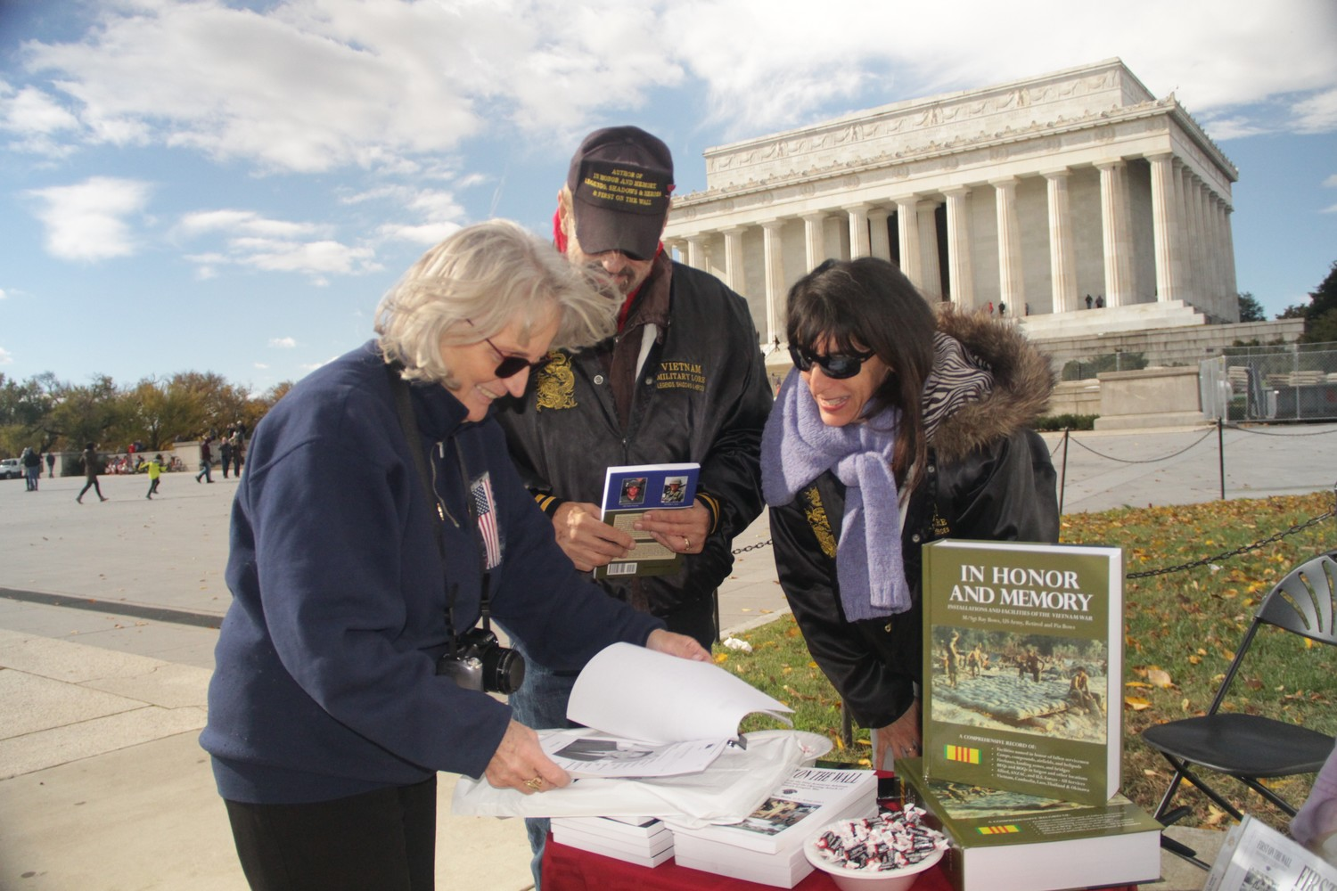 "Horn showed the authors of ""In Honor and Memory,"" Ray and Pia Bows, right, a photo of Viesturs Reikmanis, while they chatted in front of the Lincoln Memorial."