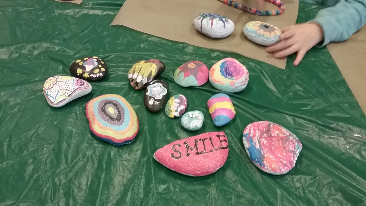Colorfully painted rocks, designed and created at an Oceanside rock painting party. Elementary schoolers, middle schoolers, and adults all pitched in to decorate the rocks.