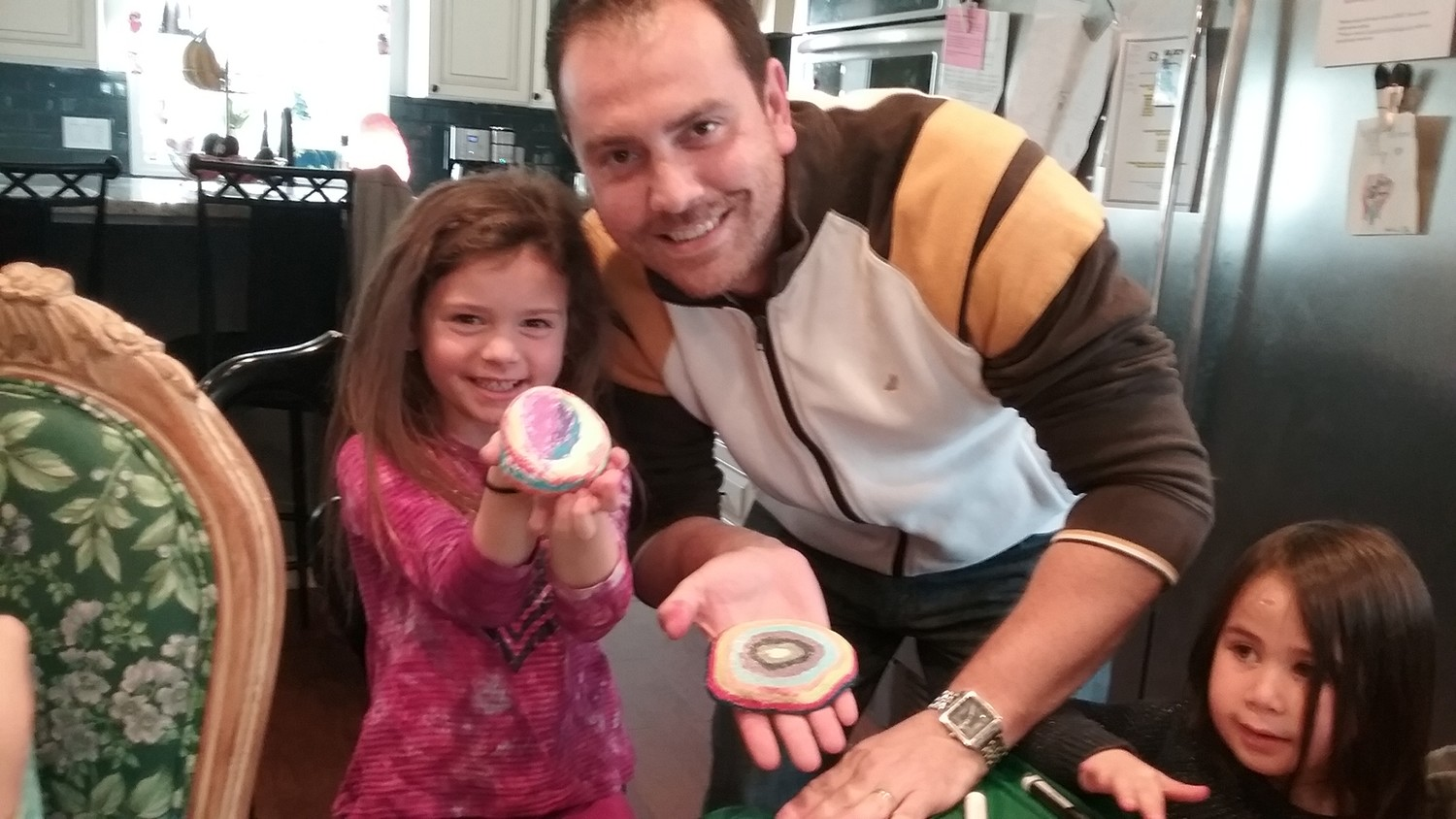 Brad Wofsy, his daughter Demi, left, and Samantha Adelman showed off the rocks they painted with bright colors in order to spread beauty, positivity and community around Oceanside.