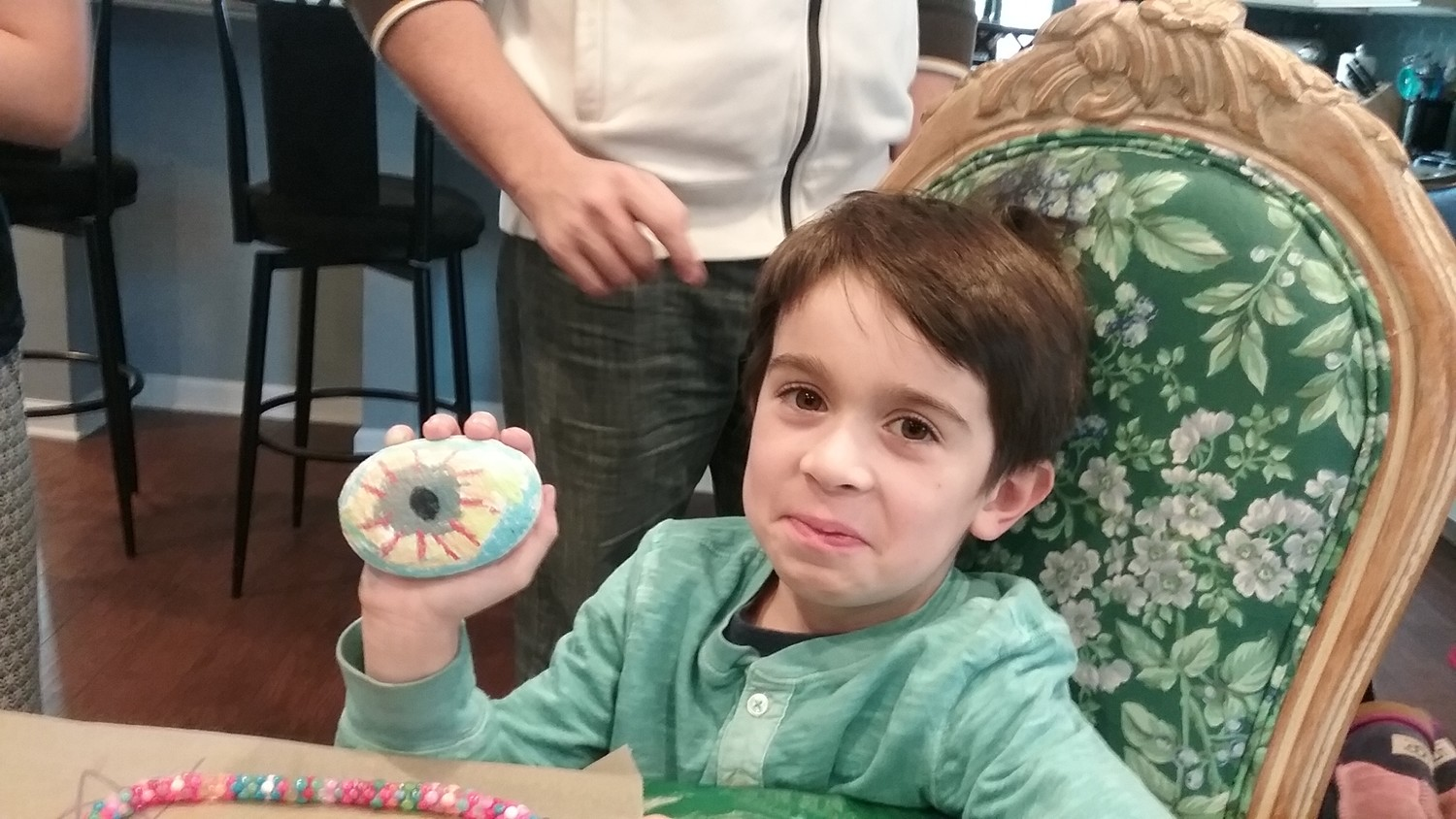 Sebastian Adelman, 6, proudly displays his creation, a colorful interplay between an eye, which takes in light, and the Sun, which emits it.