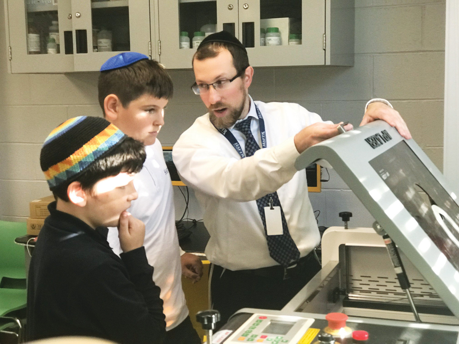 Rabbi Baruch Noy, the Hebrew Academy of the Five Towns and Rockaway's STEM curriculum coordinator, showed Peter Drukker, center, and Noah Popack how to use the state-of-the-art laser cutter in the middle school's laboratory.
