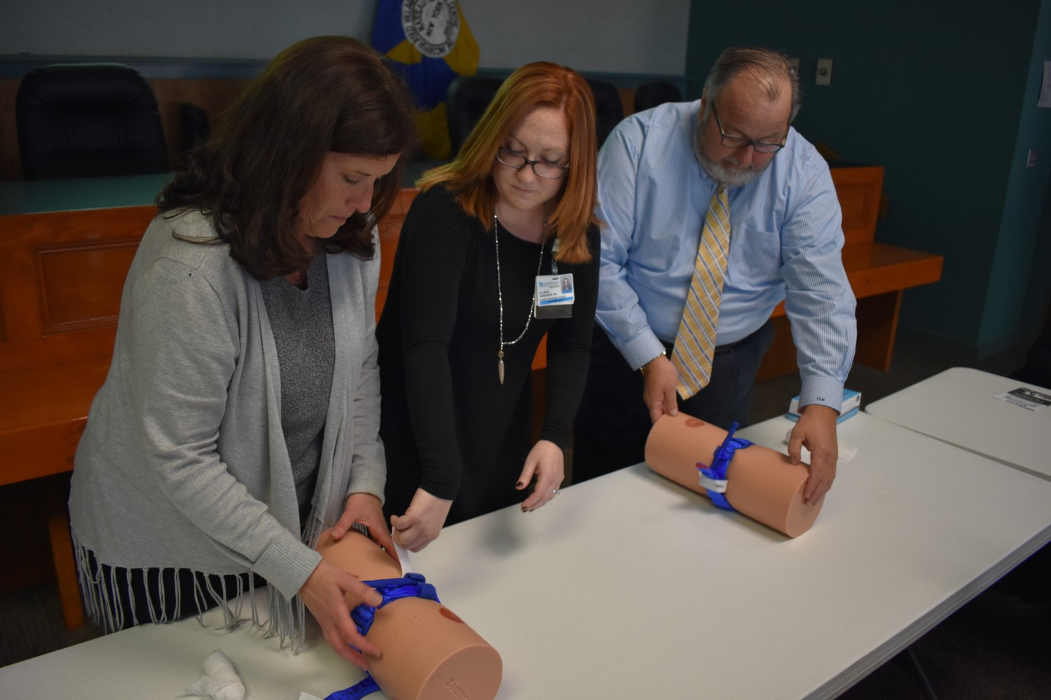 Allison Anderson, center, directed Deputy Mayor Kathy Baxley, left, and Mayor Francis Murray, right, how to stop the bleeding on life-threatening wounds.