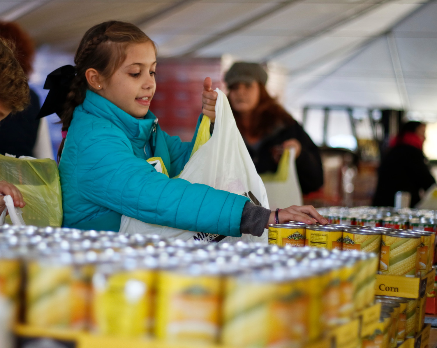 Ashley Favata, 9, from Rockville Centre Troop 828, added canned corn to one of the many bags that she and her fellow Girl Scouts packed while they volunteered at Mid Island Collision's Fill-the-Bag event on Monday, which collected Thanksgiving meals for those in need.