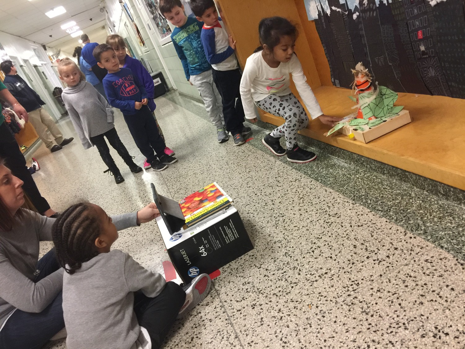 Camrin helped his teacher take stop-motion photographs of their float, which Yeimi pushed along in small increments. Sofia, far left, Ryan, Liliana, Mason and Joseph, awaited their turns.