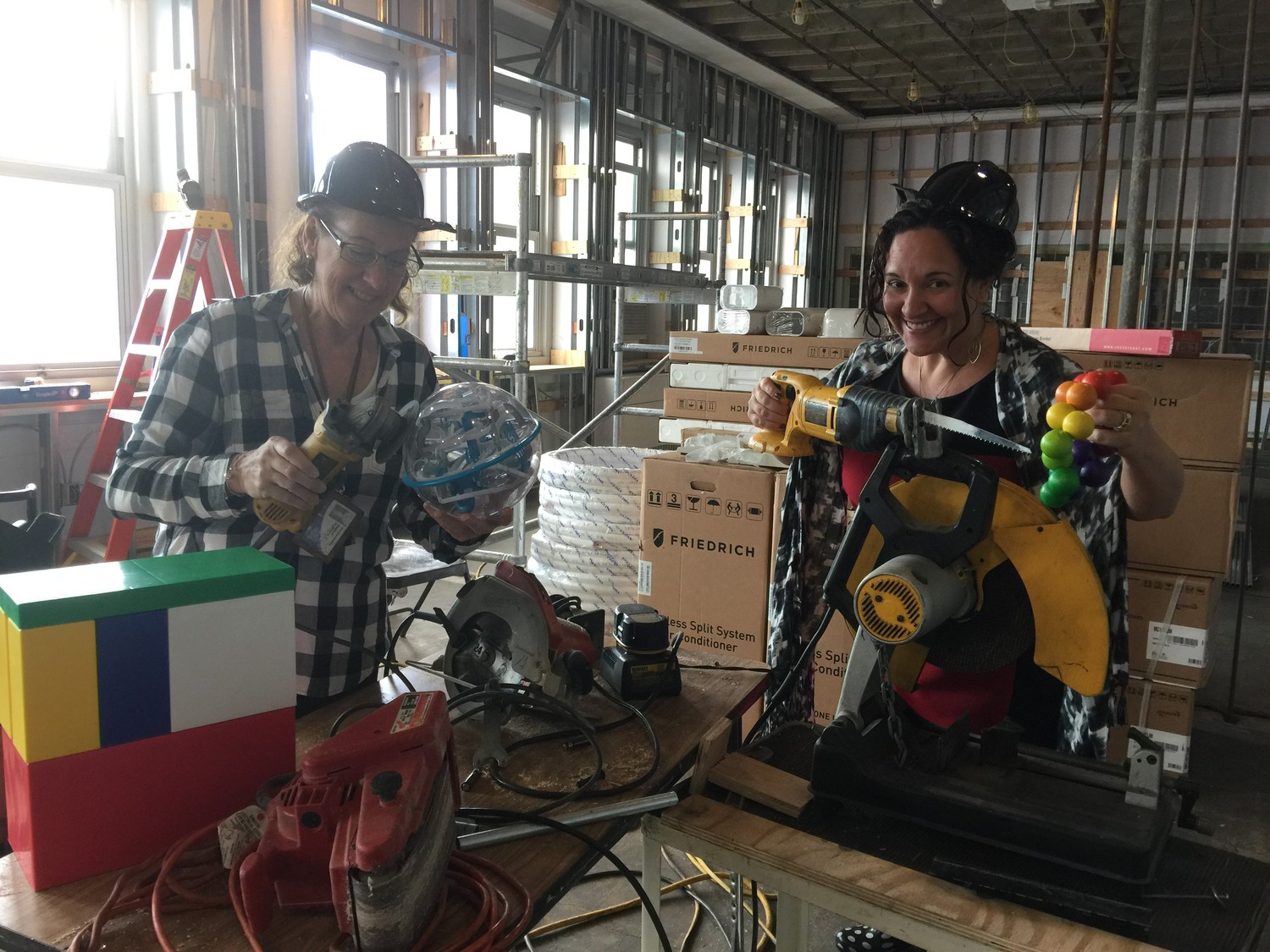 Oceanside School No. 6 principal Julie McGahan and her administrative assistant Beth Sporting in the unfinished learning lab as they pretended to build toys with power tools.