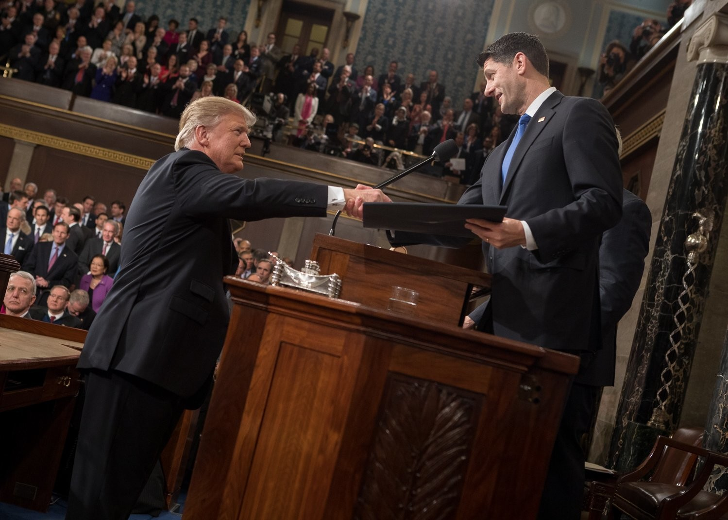 President Donald Trump, left, and Speaker of the House, Paul Ryan, shake hands on the floor of the House of Representatives