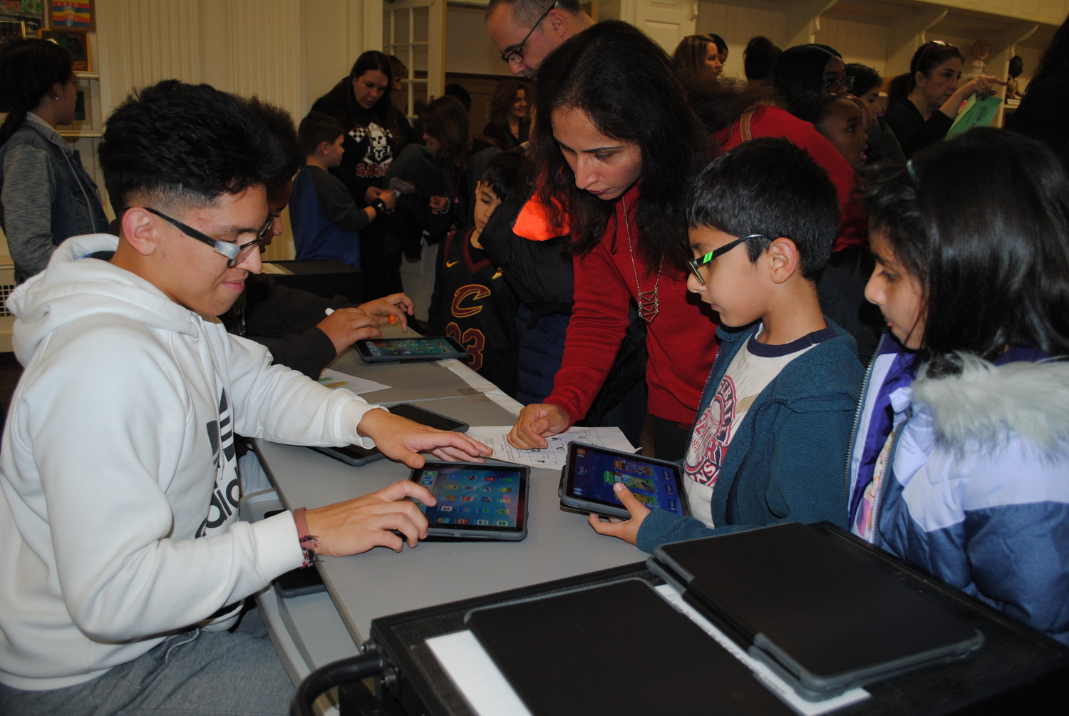 High school junior and Math Honor Society member Fernando Portillo showed Hina Asim and her children, Daniyal and Allena, how to start coding on an iPad.