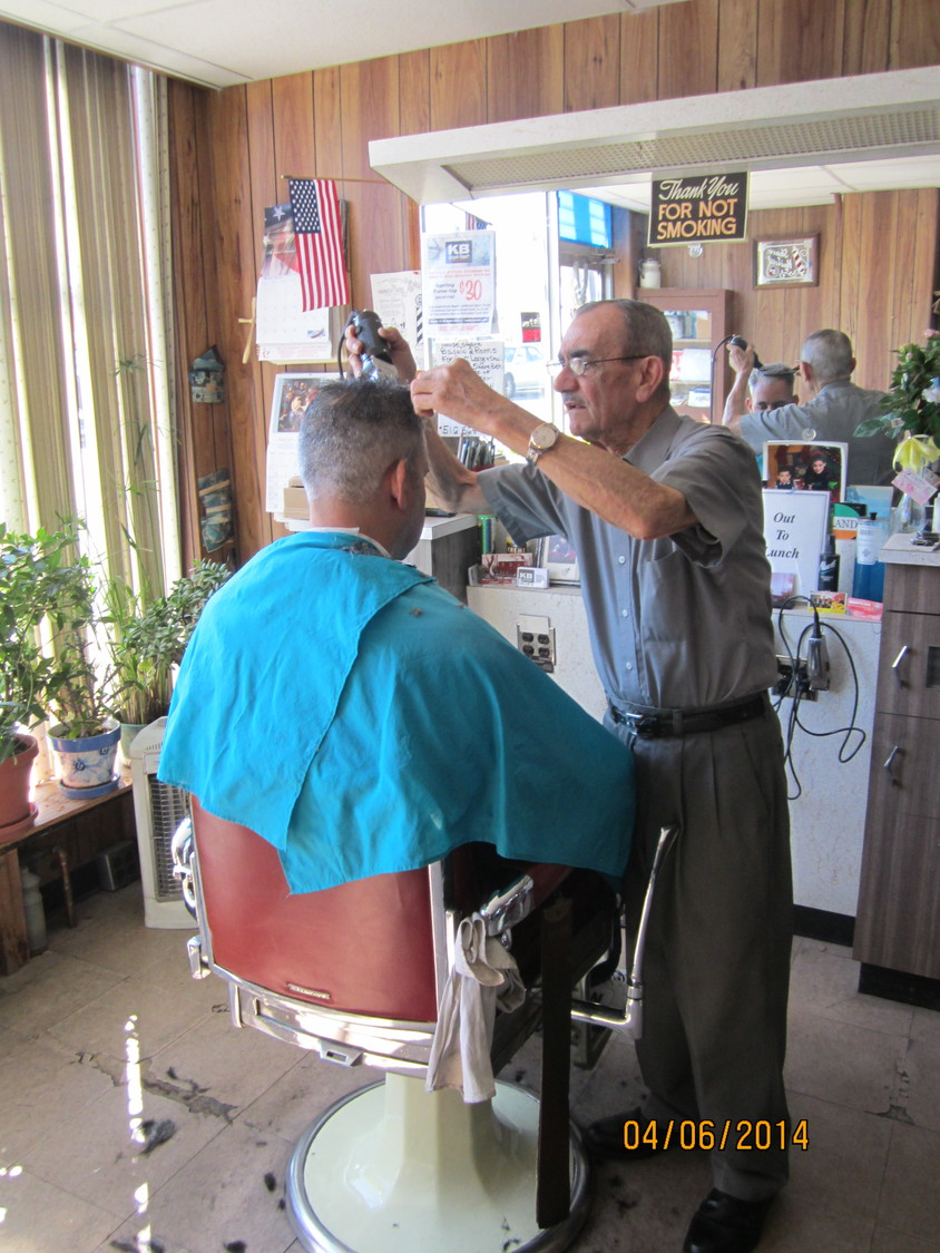 Neatale giving a haircut to one of his regular customers.