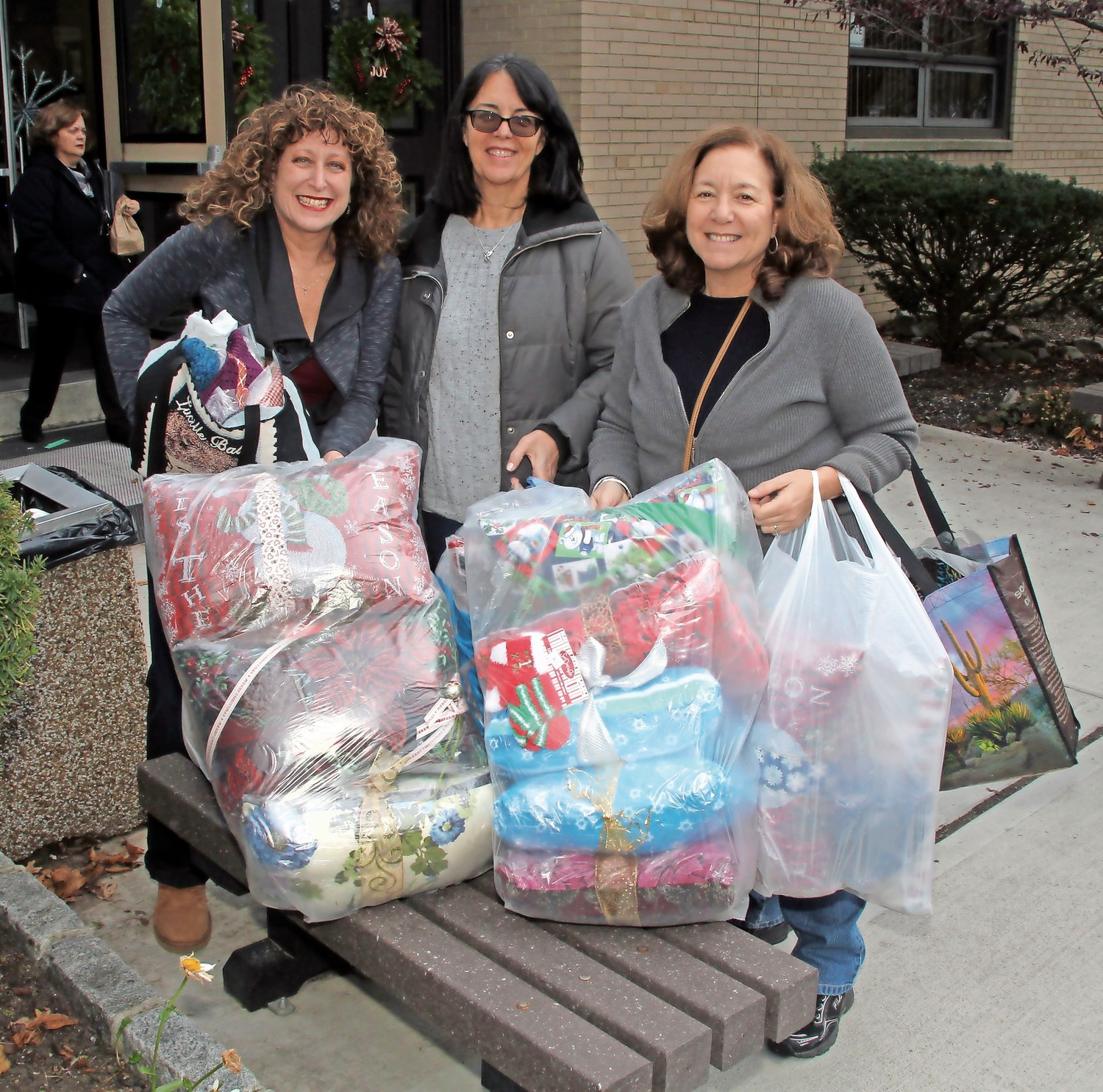 From left, Wendy Russo, Mary Jo Carson and Pam Young stocked up on some presents for the school's holiday fair.